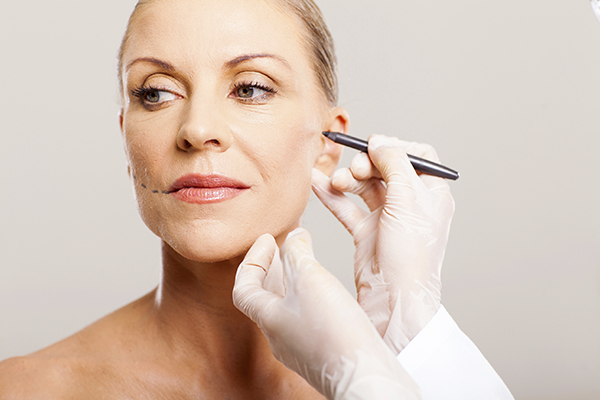 doctor correcting senior woman face